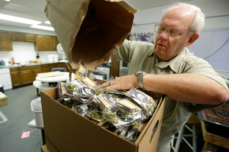 . In this July 8, 2014, photo, Bob Leeds, owner of Sea of Green Farms, pours packets of recreational marijuana into boxes at his business in Seattle for delivery to a store in Bellingham, Wash. It was the first delivery for the company since retail licenses were issued by the state on Monday, July 7. (AP Photo/Ted S. Warren)