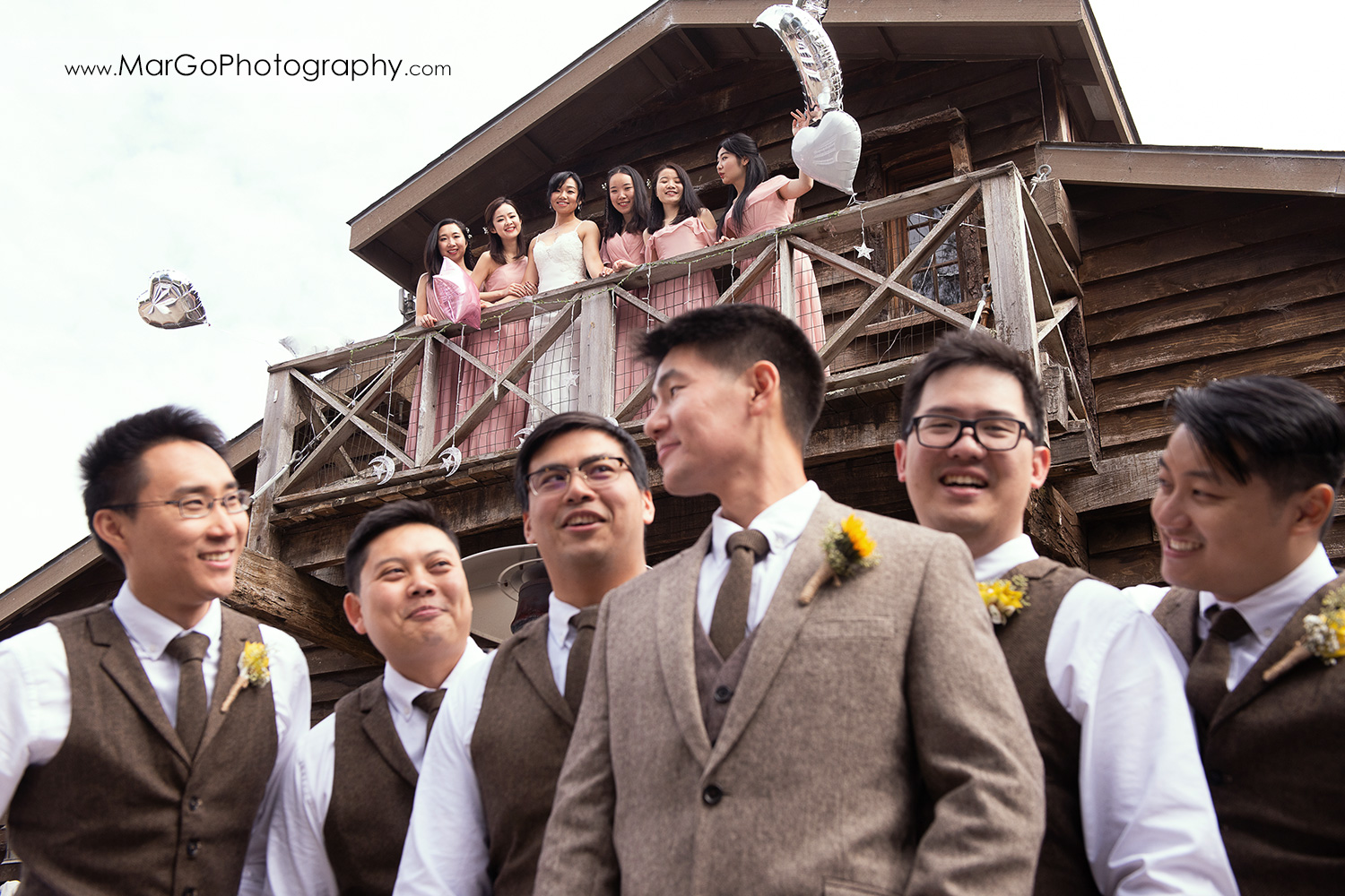 groom and groomsmen under the balcony with bride and bridesmaids in pink dresses at Long Branch Saloon & Farms in Half Moon Bay - focus on girls