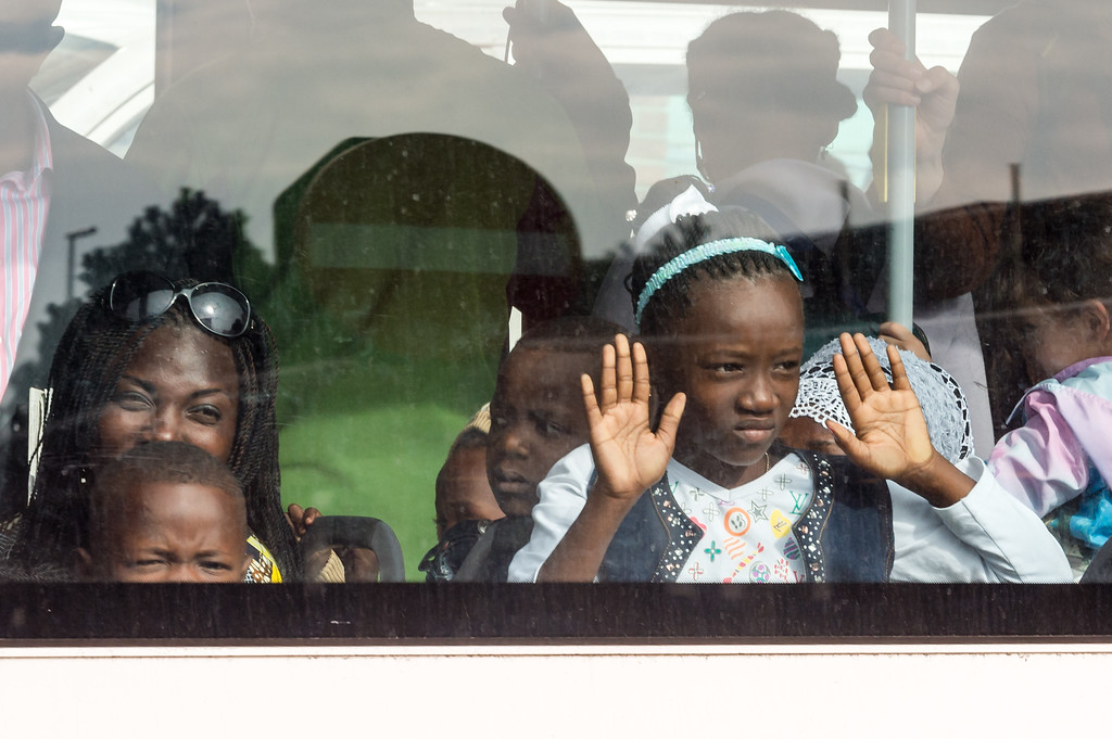 . A family look out of the window of a bus after being evacuated from Brussels airport, after explosions rocked the facility in Brussels, Belgium, Tuesday March 22, 2016. Authorities locked down the Belgian capital on Tuesday after explosions rocked the Brussels airport and subway system, killing at least 13 people and injuring many more. Belgium raised its terror alert to its highest level, diverting arriving planes and trains and ordering people to stay where they were. Airports across Europe tightened security. (AP Photo/Geert Vanden Wijngaert)