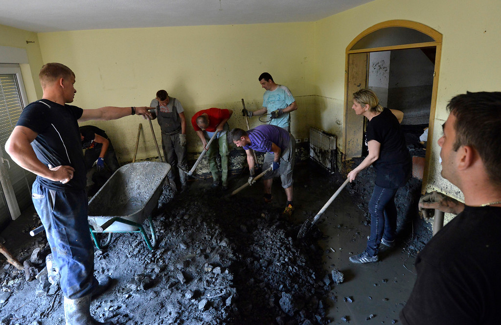 . Residents clean a house of mud and rubble after a landslide at the village of Topcic Polje, near the Bosnian town of Zenica, 90 kilometers north of Sarajevo, Bosnia-Herzegovina, Tuesday May 20, 2014. Bosnia, Serbia and Croatia have been hit by the worst flooding in more than 100 years, forcing half a million people out of their homes and leading to more than three dozen deaths. (AP Photo/Sulejman Omerbasic)