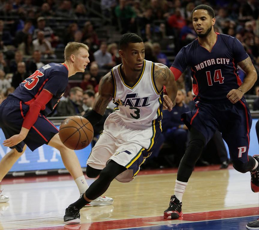 . Utah Jazz\'s Trey Burke (3) drives against Detroit Pistons\' D.J. Augustin (14) during the first half of an NBA basketball game Sunday, Nov. 9, 2014, in Auburn Hills, Mich.  (AP Photo/Duane Burleson)