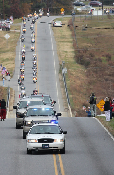 The first police car leads the precession for Staff SGT Chris Newman