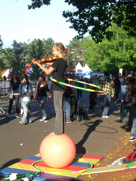 A young girl and boy were doing several things. Here, the girl was playing a violin while twirling a hoola-hoop while standing on the ball. Crazy.