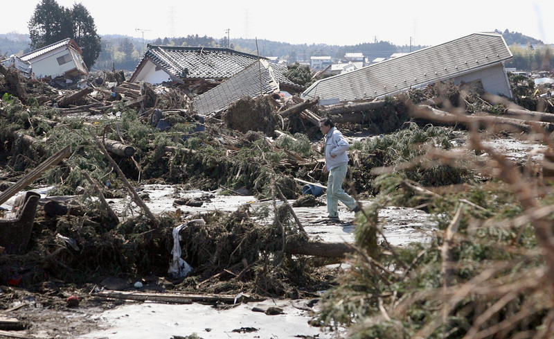 . Man walks through houses devastated by tsunami in Minami Soma, Fukushima, northern Japan Saturday, March 12, 2011 after Japan\'s biggest recorded earthquake slammed into its eastern coast Friday. (AP Photo/Kyodo News)