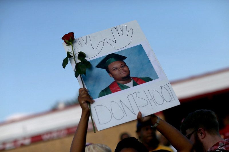""". A demonstrator holds a sign reading, \""""Dont Shoot\"""", with a picture of Michael Brown on August 17, 2014 in Ferguson, Missouri. Violent outbreaks have taken place in Ferguson since the shooting death of Michael Brown by a Ferguson police officer on August 9th.  (Photo by Joe Raedle/Getty Images)"""