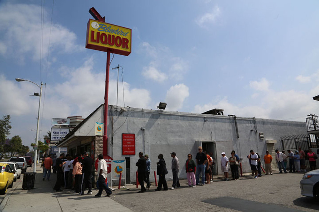 . People line up to buy lottery tickets at the Bluebird Liquor store in Hawthorne on Friday. Saturday\'s jackpot is expected to reach near $600 million. (Chuck Bennett/Staff Photographer)