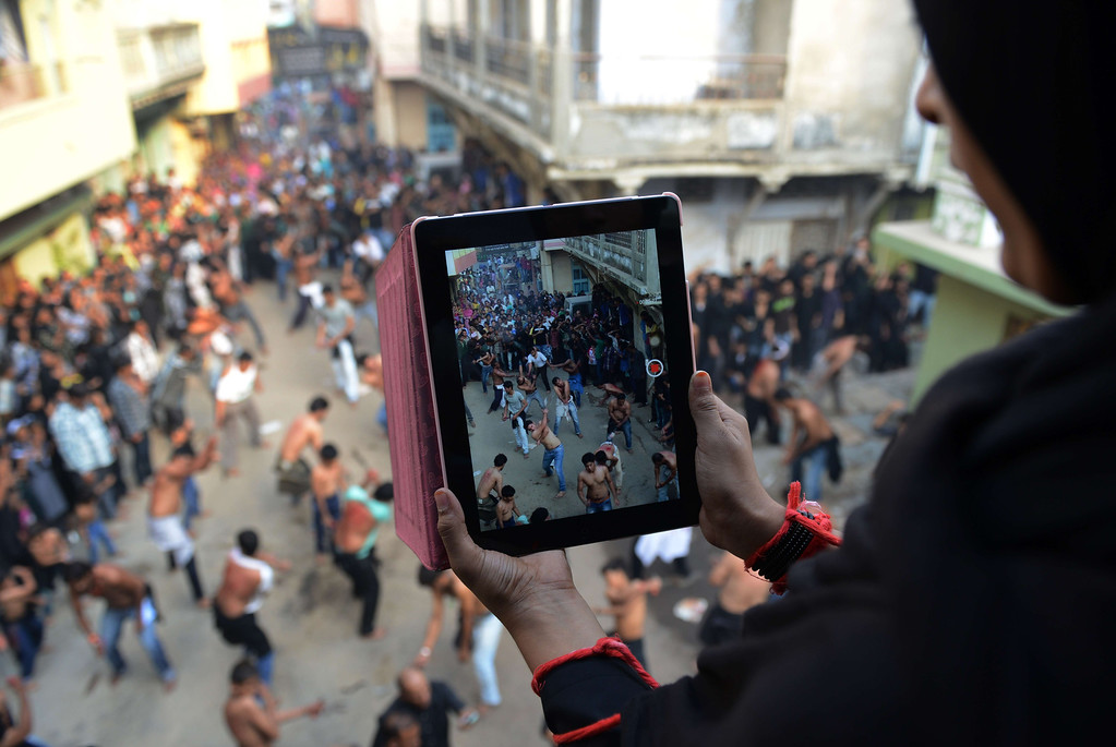 . An Indian Shiite Muslim devotee uses a tablet to film other devotees as they perform ritual self-flagellation during a Muharram procession in Ahmedabad on November 1, 2014. SAM PANTHAKY/AFP/Getty Images