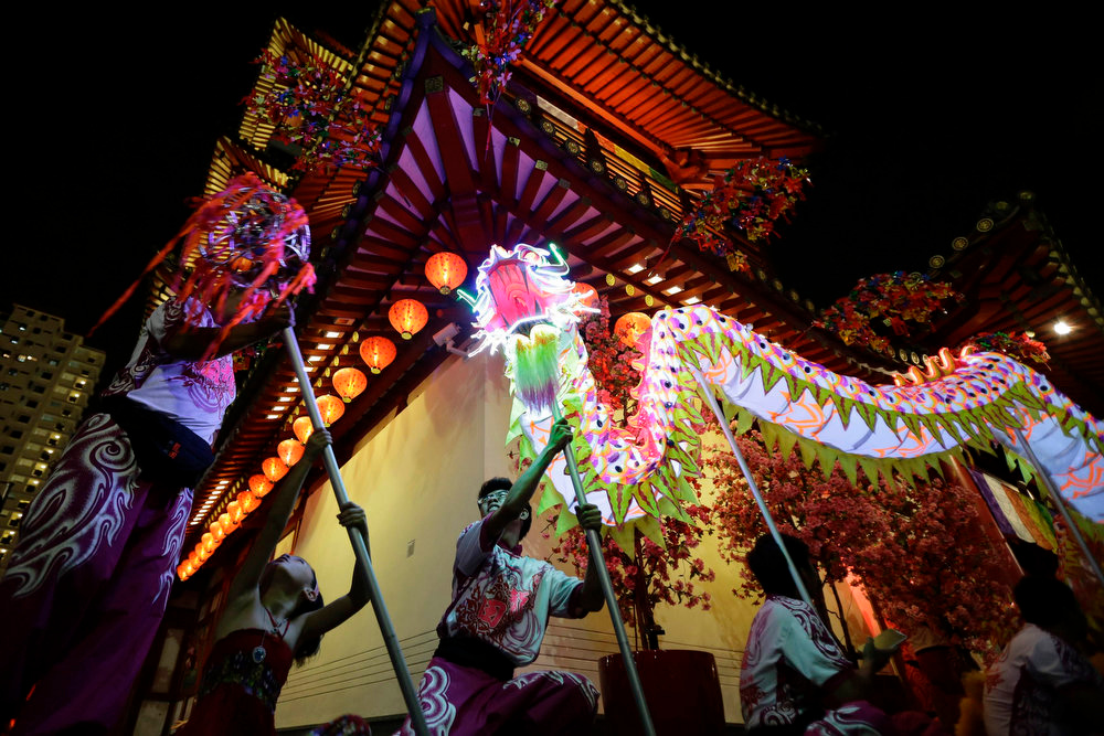 . Members of a dragon dance troupe wait outside the Buddha Tooth Temple before a ceremony during the Lantern Festival in Singapore\'s Chinatown district February 24, 2013. The festival which is also known as Yuan Xiao Jie is a Chinese festival celebrated on the 15th day of the first month of the lunar year. It also marks the end of the series of celebrations starting from the Chinese New Year. REUTERS/Tim Chong