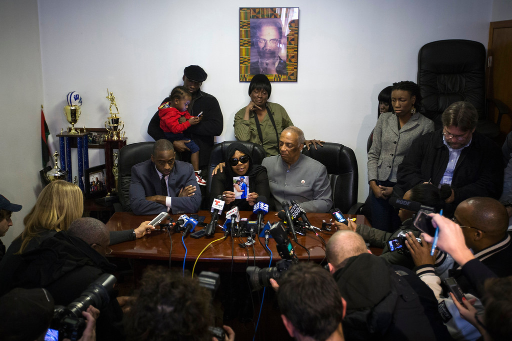 . Carol Gray (centre L) shows a photograph of her late son Kimani Gray, who was killed in a New York Police Department shooting, next to City Councilman Charles Barron (centre R) and her lawyer Kenneth Montgomery (L) during a news conference in the Brooklyn borough of New York, March 14, 2013. REUTERS/Lucas Jackson