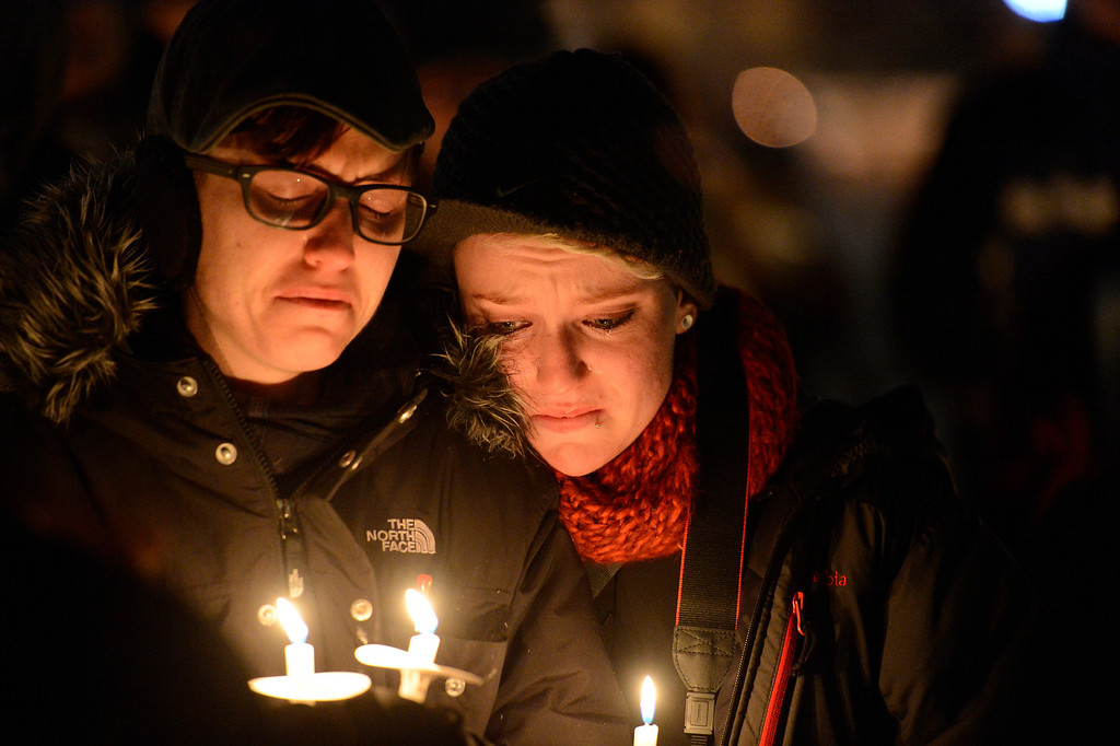 . Shannon Hogan (L) and Katie Latrell shed tears during the singing of Amazing Grace as people gathered on the steps of the City & County Building  during a candle light vigil to pay their respect to the homeless men, women and children who have passed away as they hold candles during the ceremony Wednesday, December 19, 2012. Mayor Hancock read some of the 147 names of those who have perished. John Leyba, The Denver Post