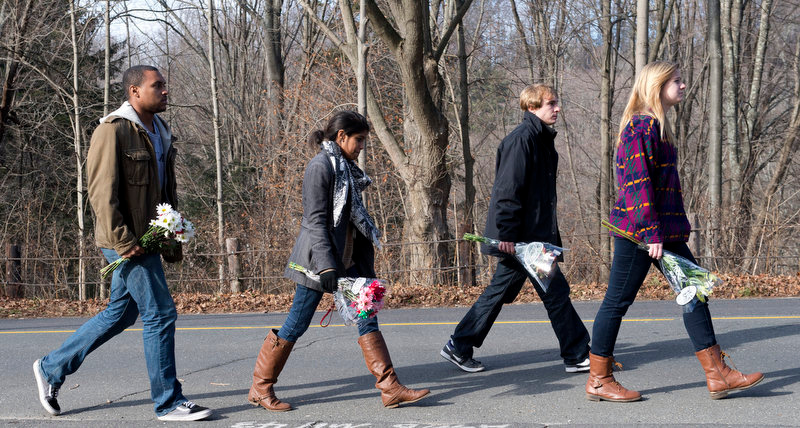 Description of . Young people carry flowers to leave near Sandy Hook Elementary School on December 15, 2012 in Newtown, Connecticut. The residents of an idyllic Connecticut town were reeling in horror from the massacre of 20 small children and six adults in one of the worst school shootings in US history. The heavily armed gunman shot dead 18 children inside Sandy Hook Elementary School, said Connecticut State Police spokesman Lieutenant Paul Vance. Two more died of their wounds in hospital.     DON EMMERT/AFP/Getty Images
