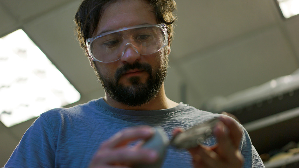 . In this June 1, 2017, photo, Metin Eren, an archaeologist at Kent State University, looks at a newly chipped flake of obsidian in Kent, Ohio. Eren runs a newly-opened laboratory which makes replicas of ancient arrows, knives, and pottery to be shot, crushed, and smashed. It\'s allowing researchers to learn about engineering techniques of the first native Americans without destroying priceless genuine relics in the process. (AP Photo/Dake Kang)