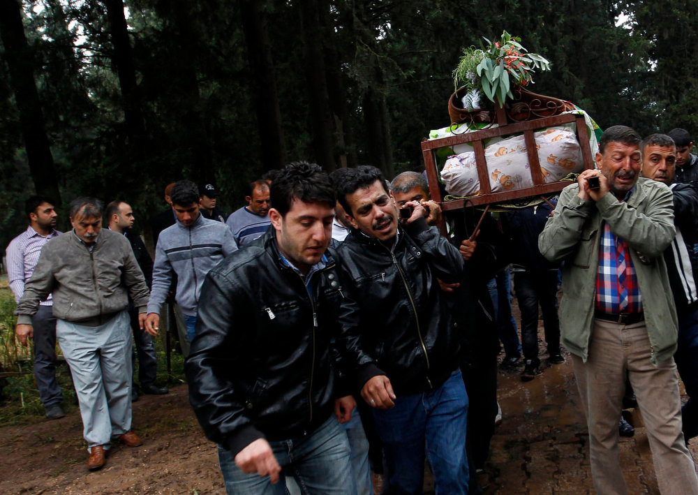 . People carry a coffin of a victim killed in yesterday\'s car bombings in the town of Reyhanli of Hatay province near the Turkish-Syrian border May 12, 2013. Turkey said on Sunday it believed fighters loyal to Syrian President Bashar al-Assad were behind twin car bombings that killed 46 people in a Turkish border town. Foreign Minister Ahmet Davutoglu said those involved in the bombings in Reyhanli on Saturday were thought also to have carried out an attack on the Syrian coastal town of Banias a week ago, in which fighters backing Assad were reported to have killed at least 62 people. Syria denied Turkish accusations on Sunday that it had a hand in twin car bombings. REUTERS/Umit Bektas