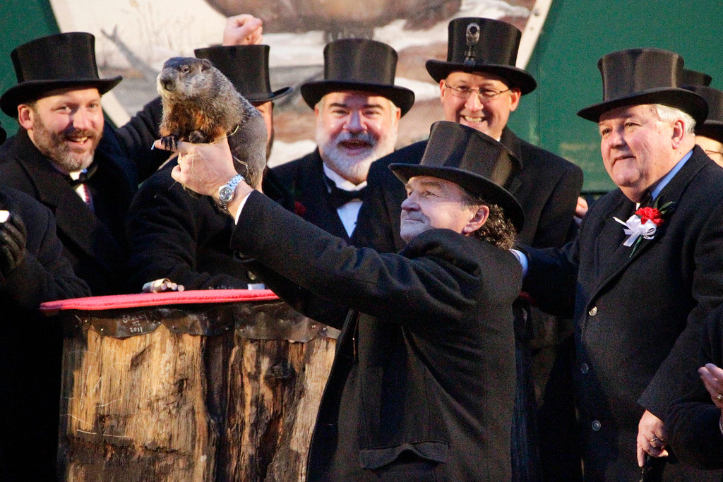 . Groundhog Club handler John Griffiths, center,  holds Punxsutawney Phil, the weather prognosticating groundhog, during the 126th celebration of Groundhog Day on Gobbler\'s Knob in Punxsutawney, Pa. Thursday, Feb. 2, 2012. Phil saw his shadow, forecasting six more weeks of winter weather. (AP Photo/Gene J. Puskar)