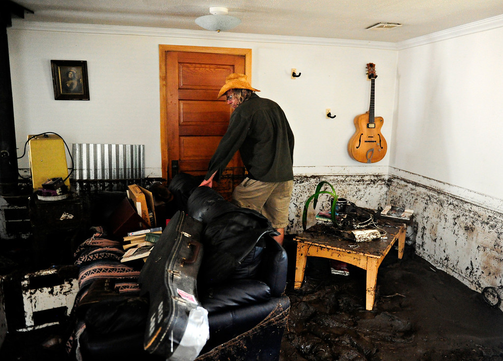 """. Gary McCrumb wades through about six inches of mud in his home, 414 Park Dr., in Lyons Friday, Sept. 13, 2013, as he collects valuables. McCrumb is planning to stay with friends in town. \""""We\'re all taking care of each other,\"""" said McCrumb. (Greg Lindstrom/Times-Call)"""