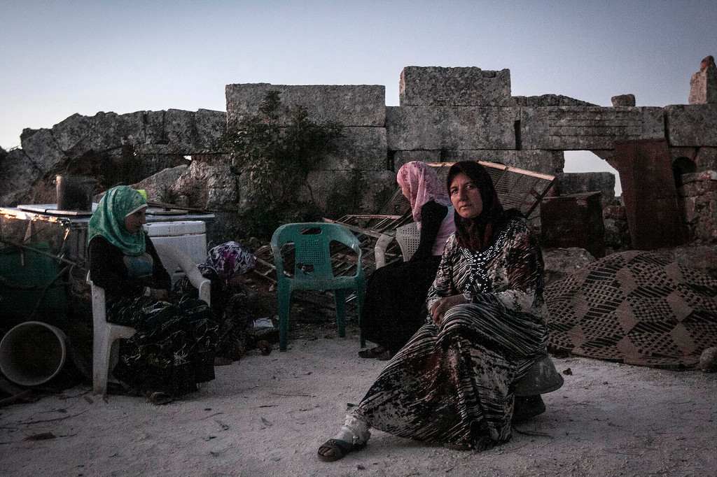 . In this Thursday, Sept. 26, 2013 photo, displaced Syrian women sit during sunset near Kafer Rouma, amid ancient ruins used as temporary shelter by those families who have fled from the heavy fighting and shelling in the Idlib province countryside of Syria. Some 2 million people have fled Syria since the countryís uprising against President Bashar Assad erupted in March 2011, according to the United Nations. Over that time, more than 4 million Syrians also have been internally displaced within the country.(AP Photo)