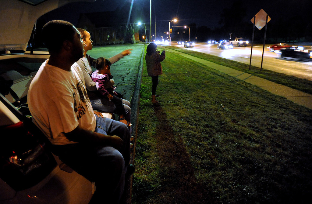 ". Robert Cato, foreground, of Pontiac, Mich., and his family (L-R): Cianna Cato, age 2; Janell Cato; and Halaya Cato, age 9, watch cars begin their turn on the Loop, along northbound Woodward Avenue.  The Cato family, who watched from the back of their vehicle in the parking lot of St. Vincent De Paul Catholic Church, watched cars from about 8:30 pm to 10:30 pm.  The reason they came out to watch the cars three days before the actual Dream Cruise was because, according to Robert, it was Halaya\'s idea to watch the cruisers at night.  Halaya also wanted to count how many ""yellow cars\"" passed them by.  Photo taken on Wednesday, August 18, 2010, in Pontiac, Mich.  (The Oakland Press/Jose Juarez)"