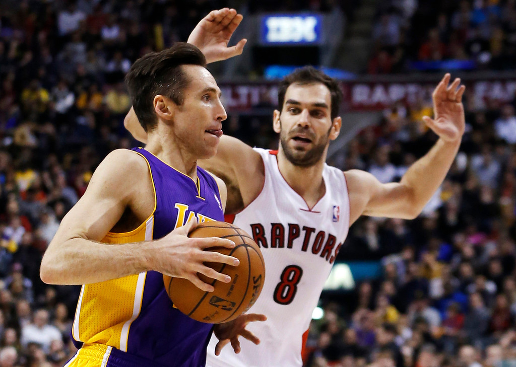 . Los Angeles Lakers\' Steve Nash drives to the net against Toronto Raptors\' Jose Calderon (R) during the first half of their NBA basketball game in Toronto, January 20, 2013.     REUTERS/Mark Blinch