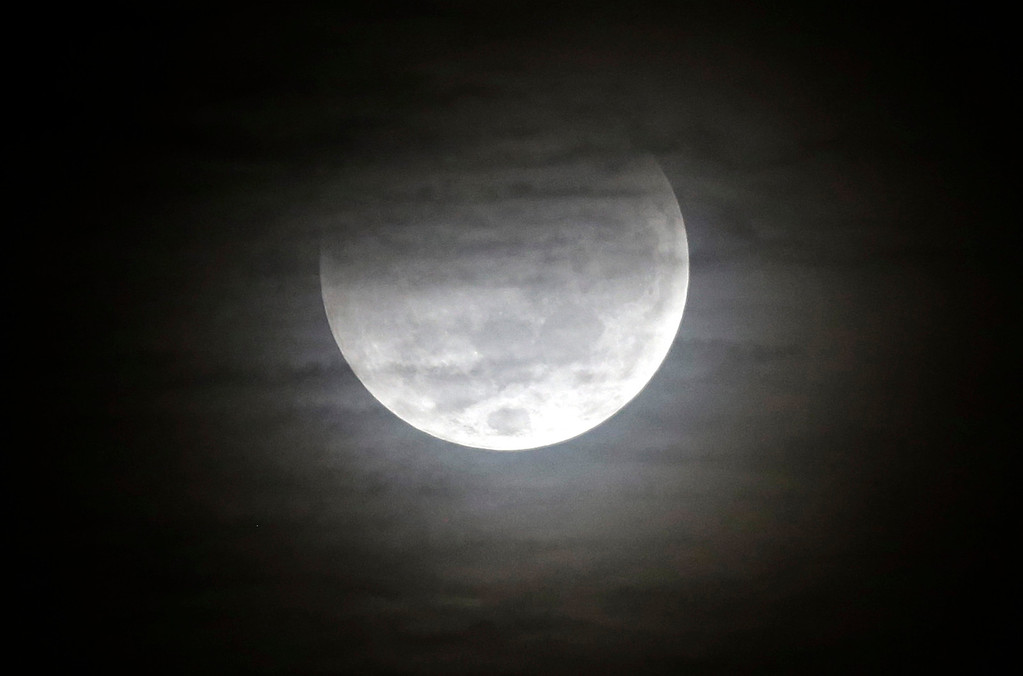 . The full moon is partially shadowed by the earth during a total lunar eclipse in Bogota, Colombia, early Wednesday, Oct. 8, 2014. (AP Photo/Fernando Vergara)