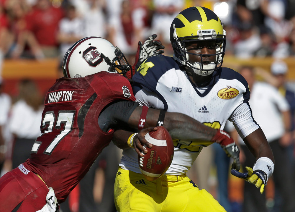 . Michigan quarterback Devin Gardner (12) is sacked by South Carolina cornerback Victor Hampton (27) during the second quarter of the Outback Bowl NCAA college football game, Tuesday, Jan. 1, 2013, in Tampa, Fla. (AP Photo/Chris O\'Meara)