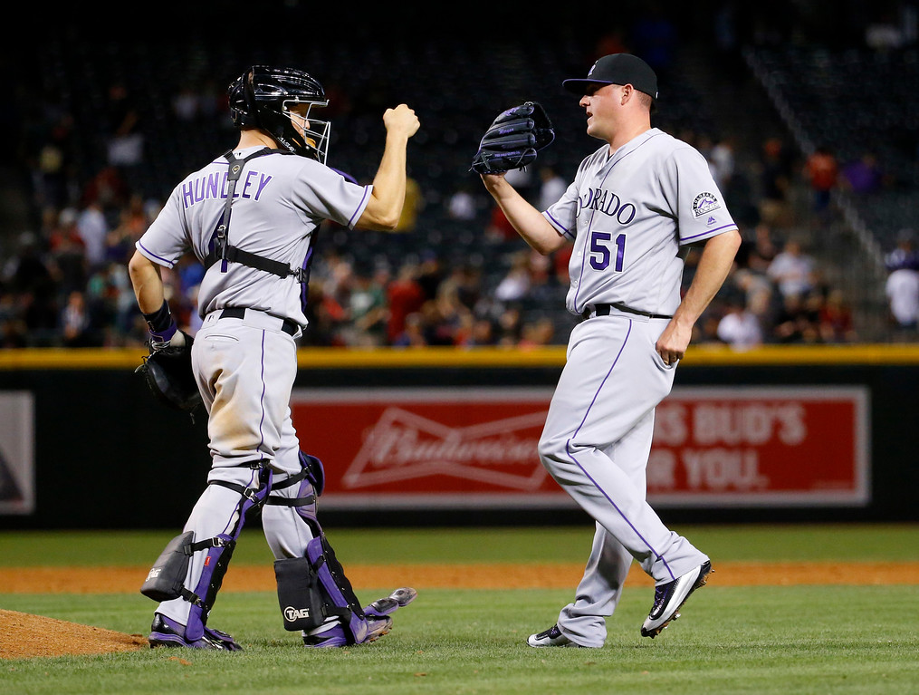 . Colorado Rockies relief pitcher Jake McGee (51) greets catcher Nick Hundley after a baseball game against the Arizona Diamondbacks, Saturday, April 30, 2016, in Phoenix. The Rockies won 5-2. (AP Photo/Matt York)