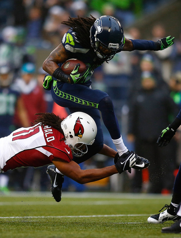. Richard Sherman #25 of the Seattle Seahawks is tackled by Larry Fitzgerald #11 of the Arizona Cardinals after makig an interception on December 22, 2013 at CenturyLink Field in Seattle, Washington.  (Photo by Jonathan Ferrey/Getty Images)