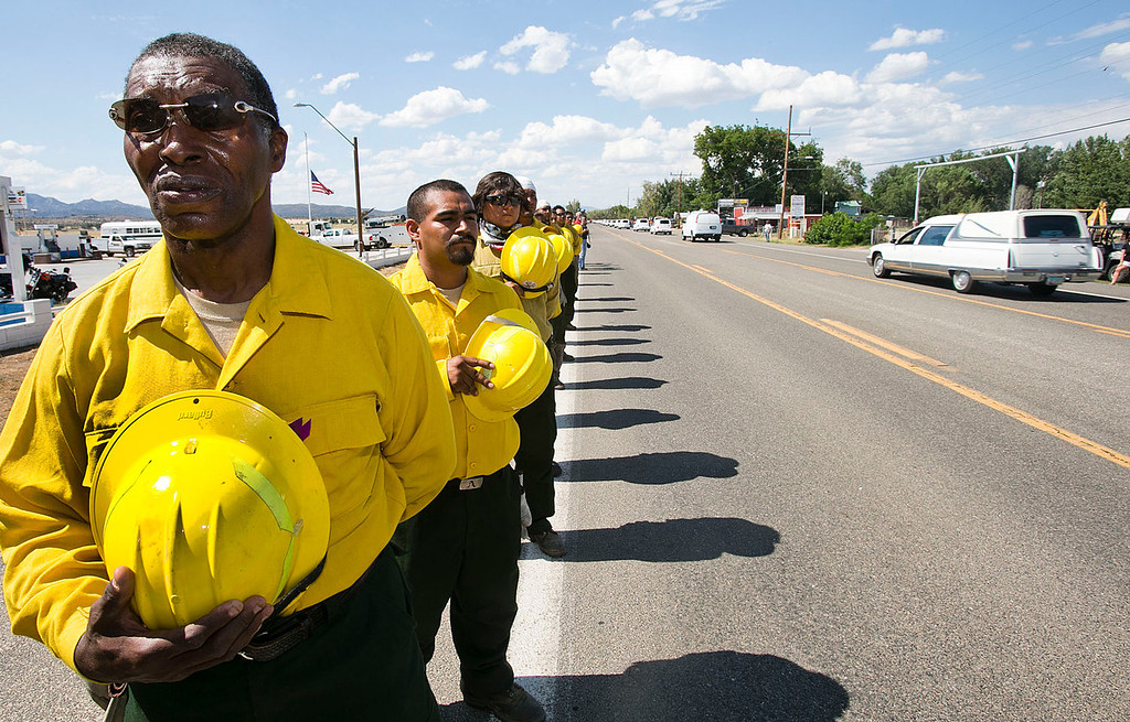 . Kenneth Salahuddin, left, crew boss for members of the Tribal Nations Response Team firefighters, pays respect to the procession of hearses carrying the 19 fallen firefighters travels through Peeple\'s Valley on highway 89 Sunday, July 7, 2013 on its way to Prescott.  The team has been fighting the Yarnell Hill Fire since July 1st. (AP Photo/The Arizona Republic, Tom Tingle)