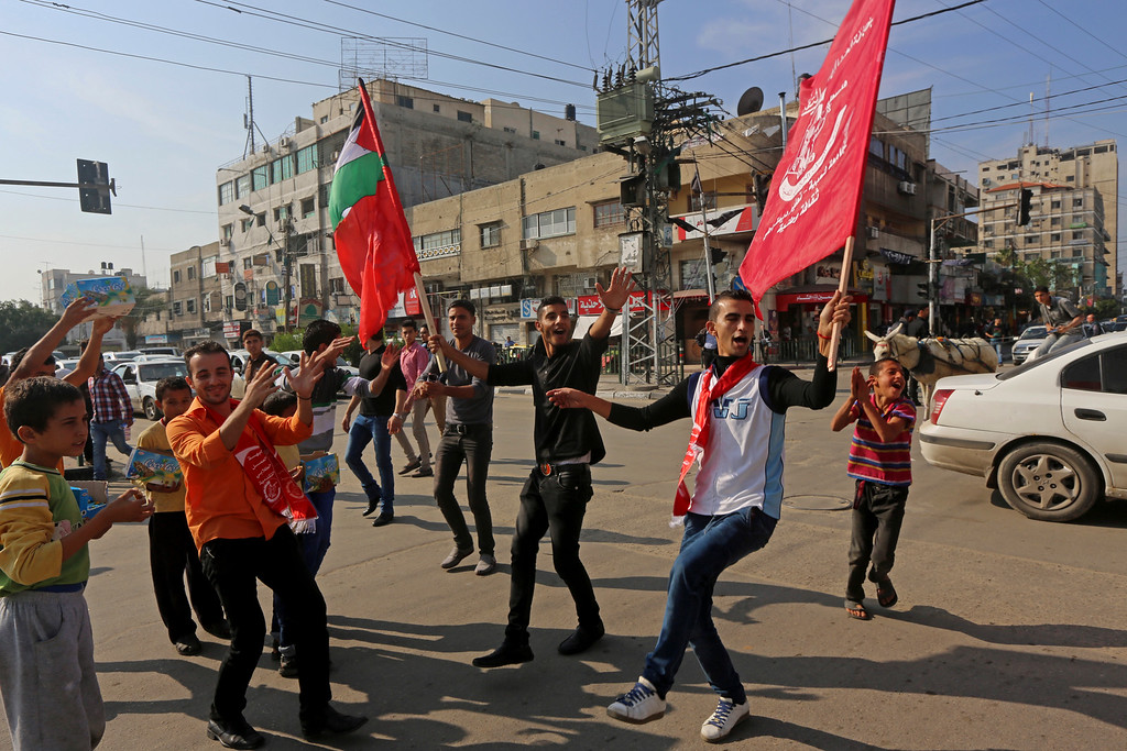 . Palestinian supporters of The Popular Front for the Liberation of Palestine, (PFLP), a small militant group, dance while waving their flags, after they heard the news of a shooting attack inside a synagogue in Jerusalem, on a main road in Gaza City, northern Gaza Strip, Tuesday, Nov. 18, 2014. Two Palestinian cousins stormed a Jerusalem synagogue on Tuesday, attacking worshippers with meat cleavers and a gun during morning prayers and killing four people in the city\'s bloodiest attack in years. The attackers were killed in a shootout with police. (AP Photo/Adel Hana)