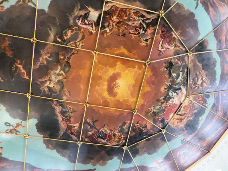 """The painting is called """"The Triumph of Religion, Arts and Science over Envy, Hate and Malice.""""  Around the border you can see a canvas cover, like the one the original Roman theater had, being drawn back to reveal the allegory.  When you climb up to the cupola of the Sheldonian, you pass through an attic where you can see some of the building's structure."""