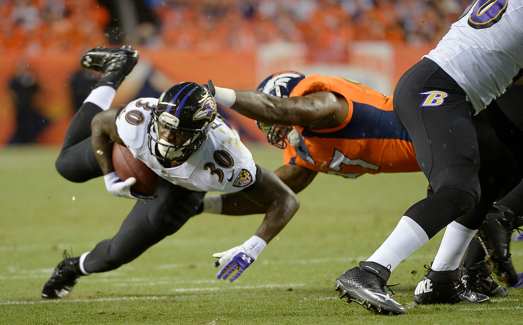 . Baltimore Ravens running back Bernard Pierce (30) is taken down in the first quarter.  (Photo by Joe Amon/The Denver Post)