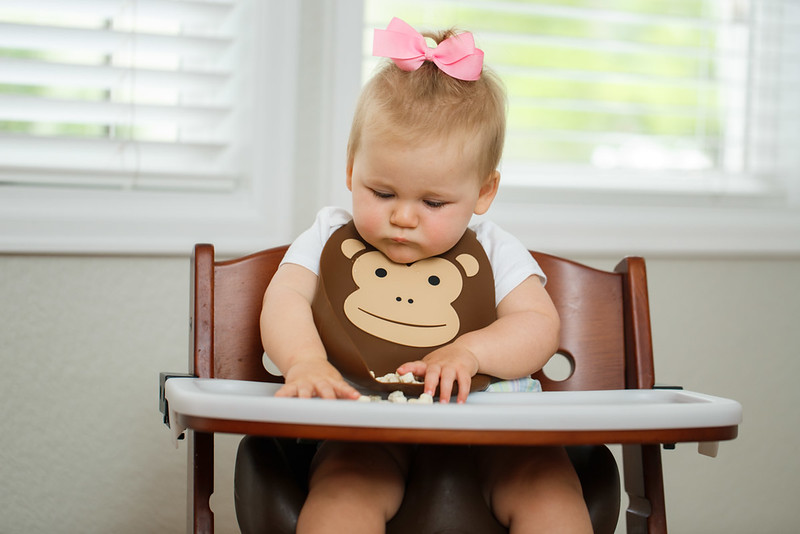 Make_My_Day_Bib_Lifestyle_Monkey_Girl_In_Highchair_Looking_At_Food.JPG