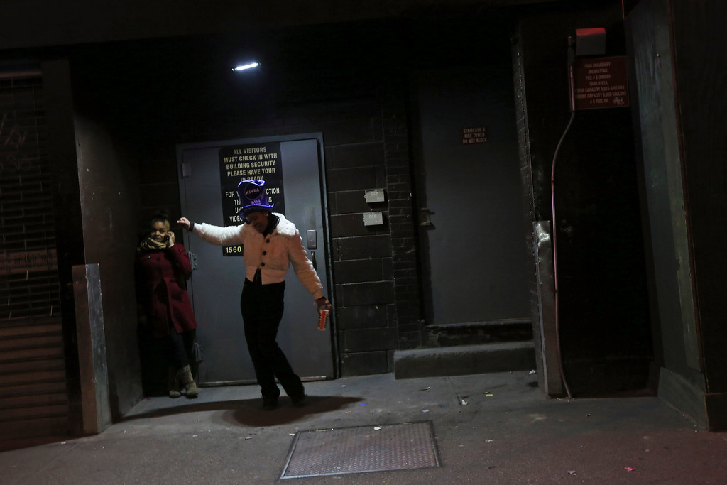 . A reveler dances in a doorway on a side street after not being allowed into the Times Square area during the New Year\'s celebration Monday, Dec. 31, 2012 in New York.  (AP Photo/Mary Altaffer)