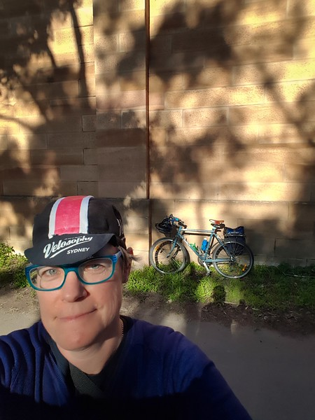 Selfie of woman in cycling cap with a bicycle leant against a sandstone wall in dappled sunlight in the background. She is on a bicycle ride in Parramatta