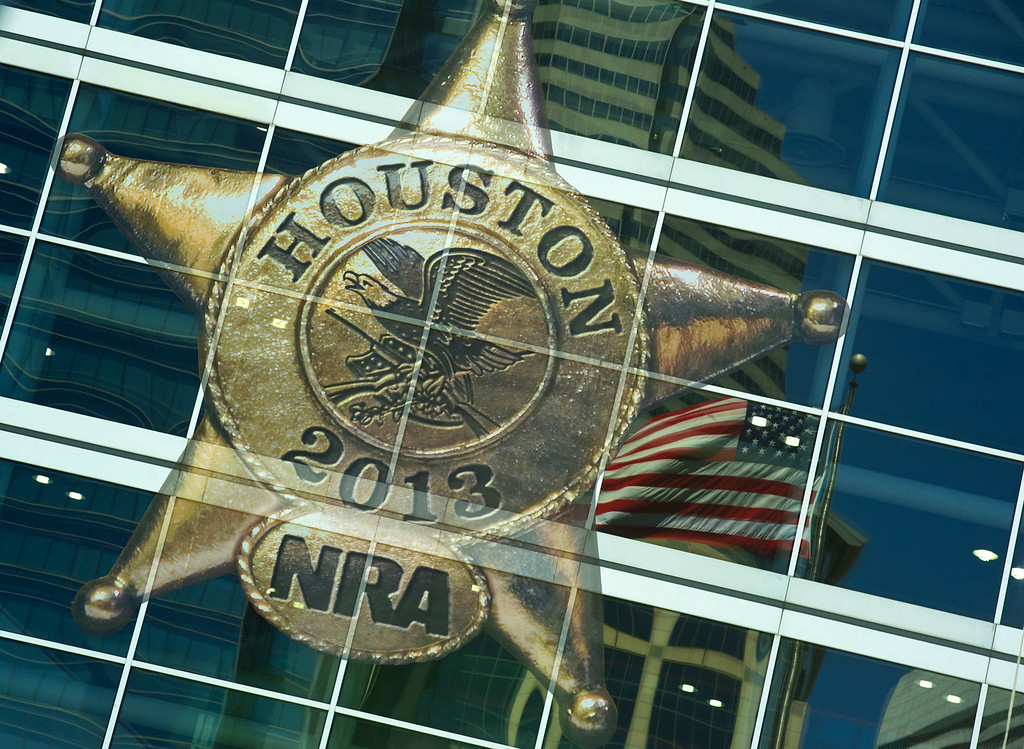. The US flag and the logo for the annual gun show are seen at the National Rifle Association (NRA) annual Convention annual on May 4, 2013 in Houston, Texas. The National Rifle Association opened its annual convention Friday in combative style, positioning itself as champion of American freedoms in the face of growing pressure for tougher gun laws. KAREN BLEIER/AFP/Getty Images
