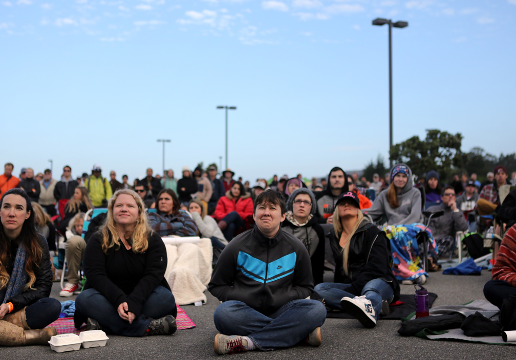 . Ellen Freytag, center, of Half Moon Bay, joins the crowd in watching the first heat of the Mavericks Invitational surfing competition form a large screen at the Mavericks Festival on Friday morning. (Kevin Johnson/Sentinel)