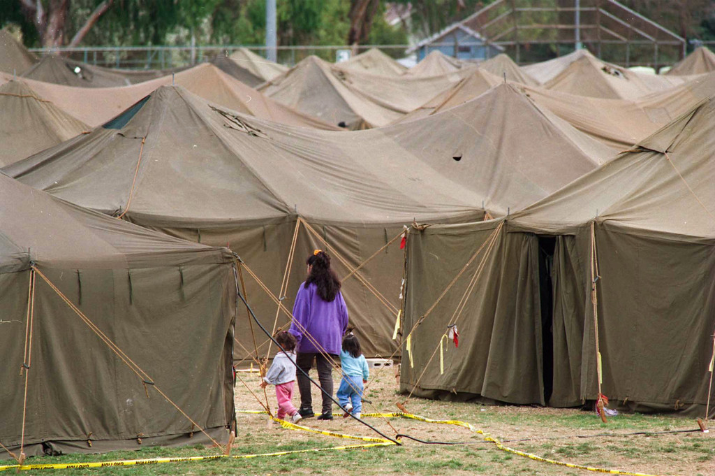 . A woman leads two children through a maze of tents set up by the National Guard for displaced quake victims at Lanark Park in Canoga Park. (Photo by Michael Owen Baker/L.A. Daily News)