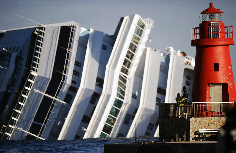 ". Firemen look at the emerged side of the cruise liner Costa Concordia on January 17, 2012. The Costa Concordia grounded in front of the harbour of Isola del Giglio after hitting underwater rocks on January 13. Rescuers searched for 29 people still unaccounted for from the wreck of a luxury liner off the coast as the arrested captain faced a hearing with investigators. ""Costa Concordia crash\"" ranked as Google\'s fifth most searched trending event of 2012. FILIPPO MONTEFORTE/AFP/Getty Images"