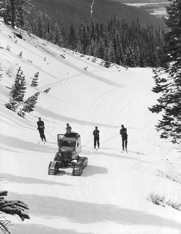 . Four members of the Rocky Mountain Park snow measuring team fan out behind their portable ski-lift, a Snow-Cat owned by Colorado Game and Fish Dept., on way to top of Trail Ridge Road in 1960. They\'re skimming along between gauging stations about half-way up, where snow is 5 to 10 feet deep on road. (Denver Post Library photo archive)