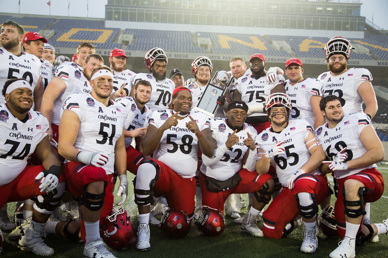 Cincinnati players celebrate with the Military Bowl trophy
