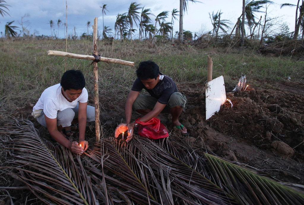 . Relatives light candles for victims of Typhoon Haiyan at a makeshift grave site on a field in Palo town, Leyte province, central Philippines on Saturday, Nov. 16, 2013. (AP Photo/Aaron Favila)