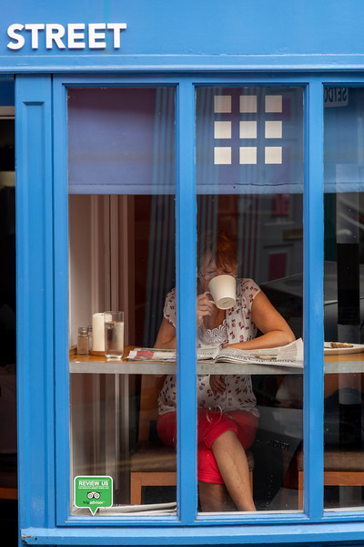 Woman drinking coffee in a caf�, Kinsale, County Cork, Ireland