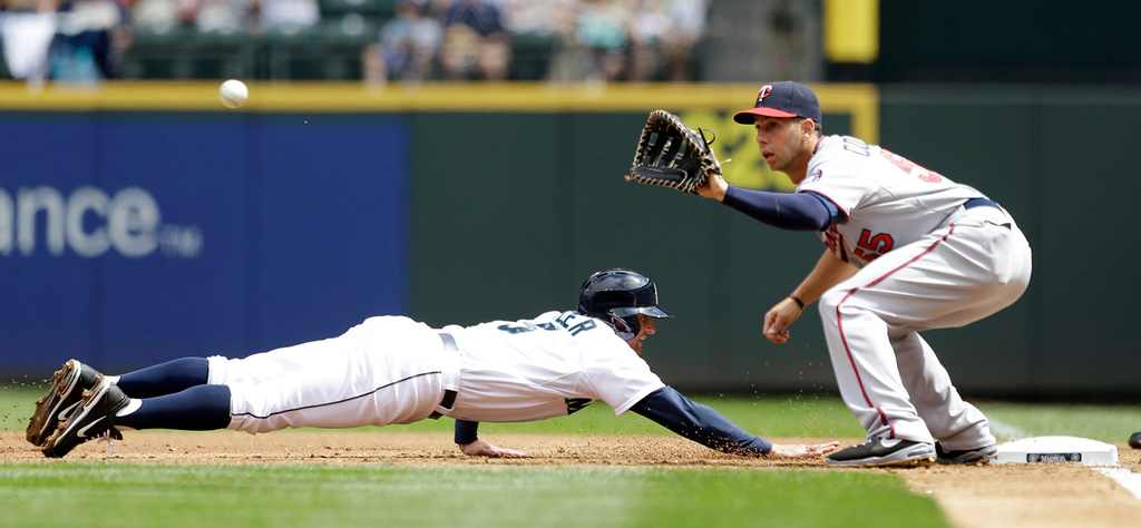 . Seattle\'s Brad Miller, left, dives safely back to first on a pick-off attempt as Twins first baseman Chris Colabello draws a bead on the throw in the first inning. (AP Photo/Elaine Thompson)