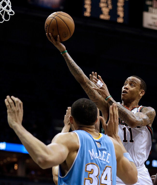 . Milwaukee Bucks\' Monta Ellis (11) shoots against Denver Nuggets\' JaVale McGee (34) during the second half of an NBA basketball game on Monday, April 15, 2013, in Milwaukee. (AP Photo/Jeffrey Phelps)