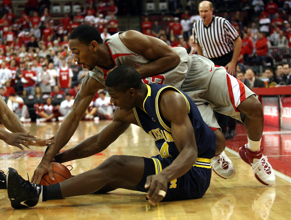 . Michigan\'s DeShawn Sims, on the floor, battles Ohio State\'s David Lighty, top, for a loose ball during the first half of a basketball game Tuesday, Feb 6, 2007, in Columbus, Ohio. (AP Photo/Terry Gilliam)