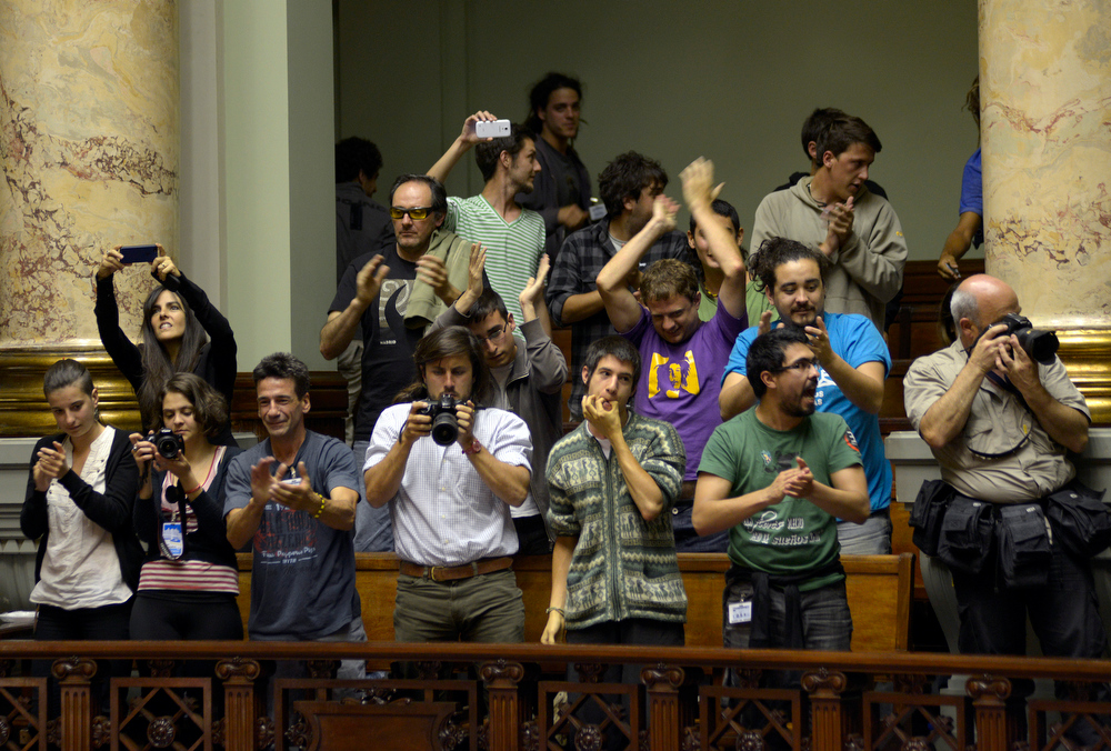 . People celebrate as senators approve a government-run marijuana industry in Montevideo, Uruguay, Tuesday, Dec. 10, 2013. Uruguay\'s Senate approved the world\'s first national marketplace for legal marijuana Tuesday, an experiment that puts the government in charge of growing, selling and using a drug that is illegal almost everywhere else. (AP Photo/Matilde Campodonico)