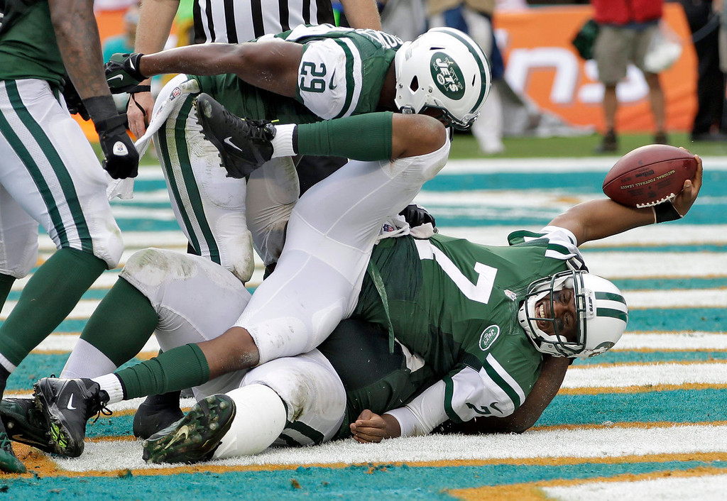 . New York Jets quarterback Geno Smith (7) celebrates after diving into the end zone to score on a 7-yard touchdown run in the second quarter of an NFL football game against the Miami Dolphins Sunday, Dec. 29, 2013, in Miami Gardens, Fla. (AP Photo/Alan Diaz)