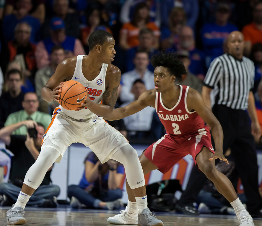 . Florida forward Keith Stone (25) looks to pass around Alabama guard Collin Sexton (2) during the first half of an NCAA college basketball game in Gainesville, Fla., Saturday, Feb. 3, 2018. Alabama won 68-50. (AP Photo/Ron Irby)