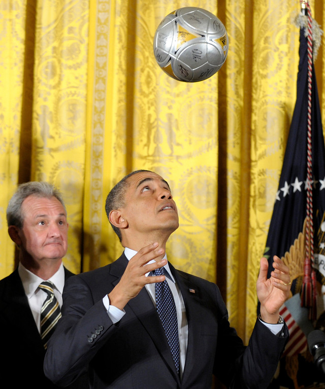 . Los Angeles Kings hockey coach Darryl Sutter watches as President Barack Obama bounces a soccer ball off of his head during an event to honor the 2012 championship seasons of the Stanley Cup champion Los Angeles Kings and the Major League Soccer champion Los Angeles Galaxy, Tuesday, March 26, 2013, in the East Room of the White House in Washington. (AP Photo/Susan Walsh)