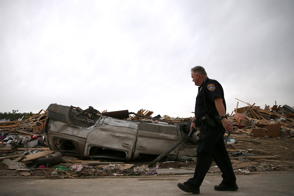 . A police officer walks past an overturned car at a homesite that was destroyed by a tornado on Sunday, April 29, 2014 in Vilonia, Arkansas.  (Photo by Mark Wilson/Getty Images)