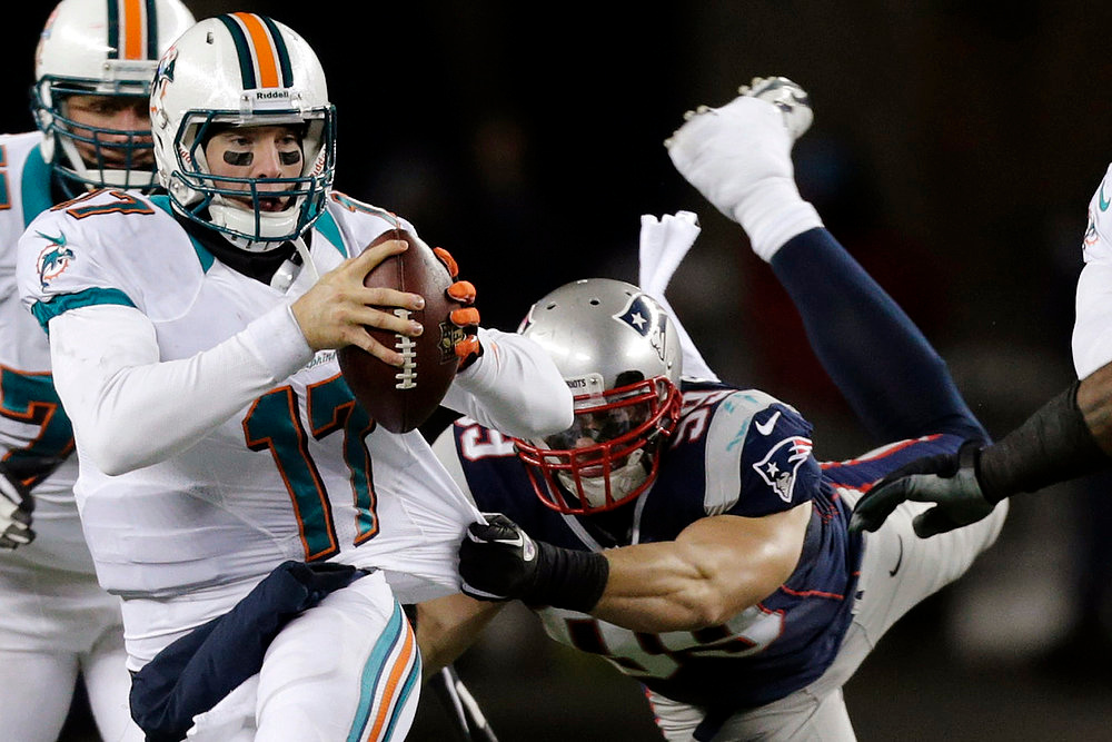 . New England Patriots defensive end Trevor Scott (99) tries to tackle Miami Dolphins Quarterback Ryan Tannehill (17) during the third quarter of an NFL football game in Foxborough, Mass., Sunday, Dec. 30, 2012. (AP Photo/Charles Krupa)